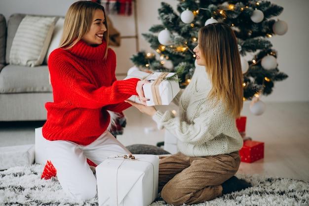 Twee meisjesvrienden met kerstcadeautjes bij de kerstboom
