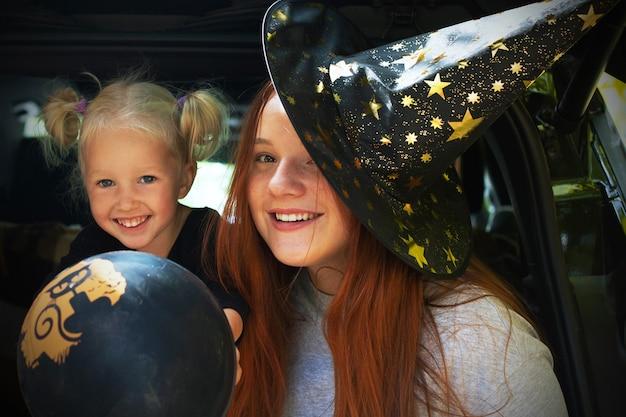 Twee meisjeszusjes die halloween-kofferbak vieren met plezier