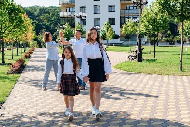 Twee meisjeszusjes houden elkaars hand vast en gaan naar school terwijl hun ouders zich verheugen