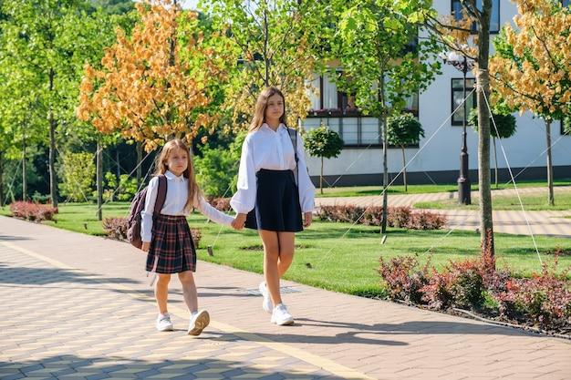 Twee meisjeszusjes houden elkaars hand vast en gaan 's ochtends samen naar school