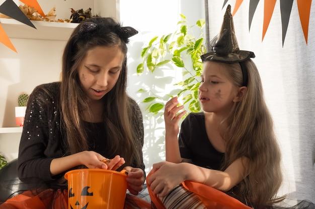 Twee meisjeszusters van tien en zeven jaar oud in heksenkostuums op halloween vieren de vakantie om