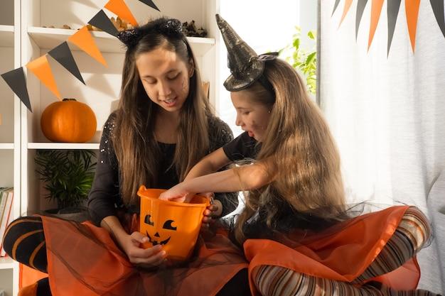 Twee meisjeszusters van tien zeven jaar oud in heksenkostuums op halloween vieren thuis vakantie