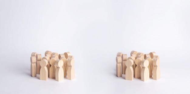 Twee menigten van houten figuren van mensen staan op een witte achtergrond.