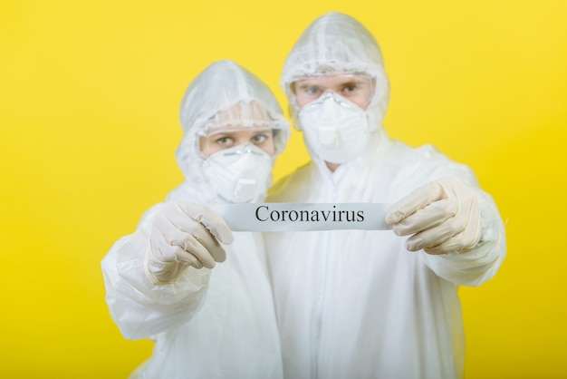 Twee menselijke artsen, uitgerust in een persoonlijk beschermend pak (pbm), houden een waarschuwingsbord vast met de tekst coronavirus. gele achtergrond