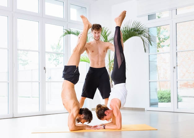 Twee mensen die een yoga pincha mayurasana uitvoeren met hulp
