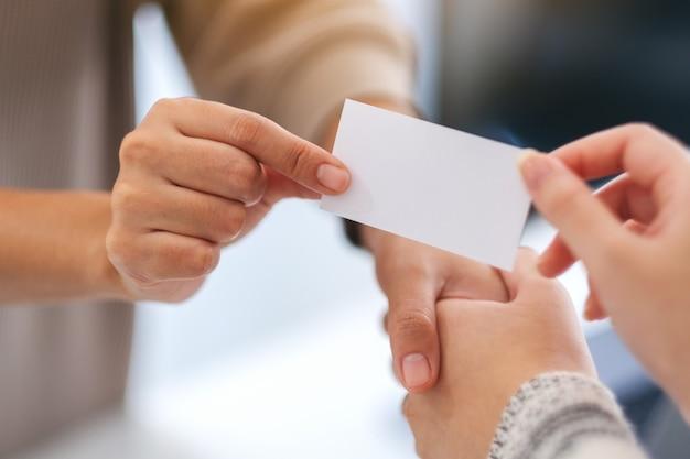 Twee mensen die elkaar de hand schudden en een leeg visitekaartje uitwisselen