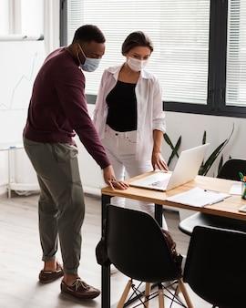 Twee mensen die op kantoor werken tijdens een pandemie met maskers aan