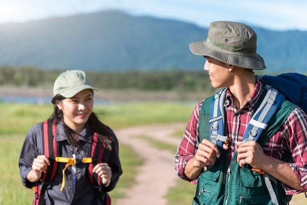 Twee mensen die op weg op weidegebied lopen. mannelijke en vrouwelijke reiziger die aantrekkelijkheid bekijkt Premium Foto
