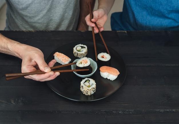 Twee mensen die sushi eten.