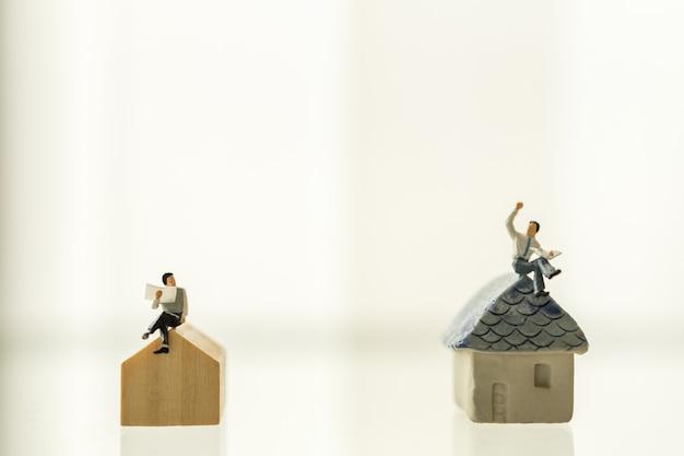 Twee mensen die van het zakenman miniatuurcijfer en krant zitten lezen en op minihuisstuk speelgoed exemplaarruimte spreken.