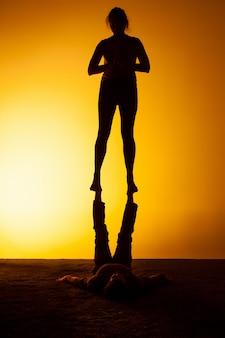 Twee mensen die yoga in het zonsonderganglicht uitoefenen