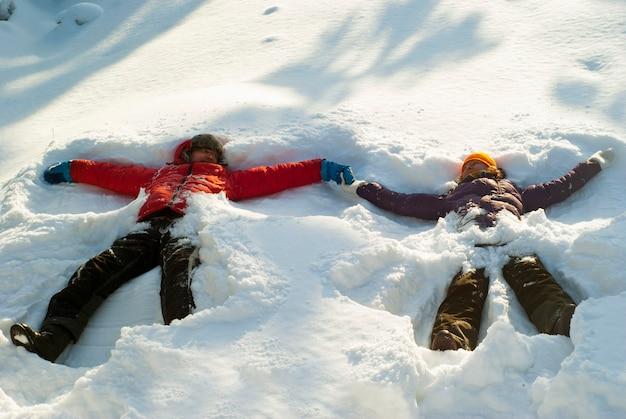 Twee mensen een man en een vrouw maken sneeuwengelen in een diepe sneeuwbank, hand in hand