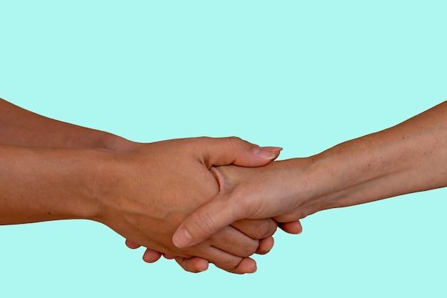 Twee mensen hand in hand, ouderen en jongeren handen schudden, helpende hand en wereldvrede concept met kopie ruimte. blauwe muur.