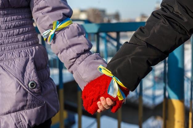 Twee mensen houden elkaars hand vast. blauwe en gele linten zijn in hun handen gebonden. symbolisch voor oekraïne