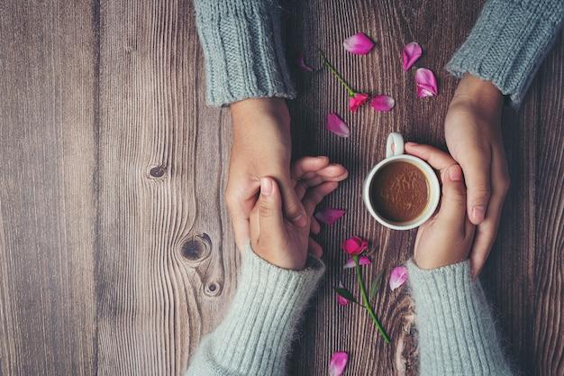 Twee mensen houden van kopje koffie in handen met liefde en warmte op houten tafel