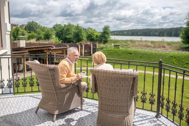 Twee mensen in de rieten fauteuils zittend op het terras