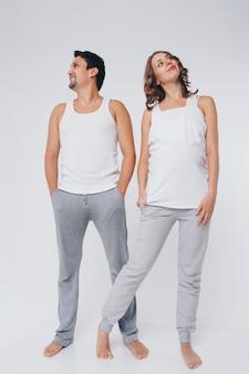 Twee mensen in identieke poses. een man en een zwangere vrouw zien er heel anders uit. het concept van een gezonde spijsvertering, levensstijl