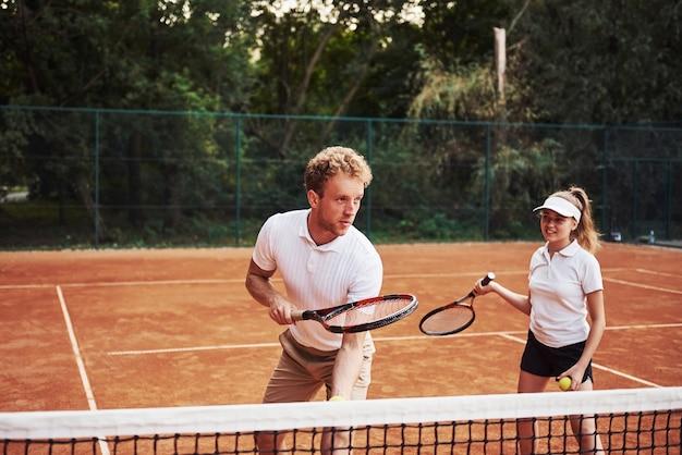 Twee mensen in sportuniform spelen samen tennis op het veld.