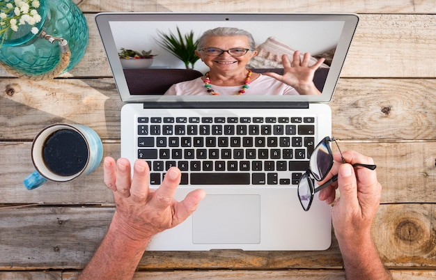 Twee mensen in videogesprek met laptopcomputer. glimlachende oudere vrouw