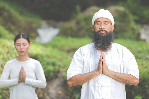Twee mensen in witte outfit die in de natuur mediteren