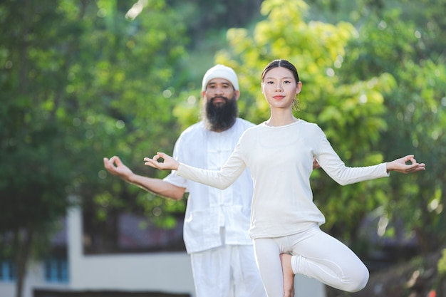 Twee mensen in witte outfit doen yoga in de natuur