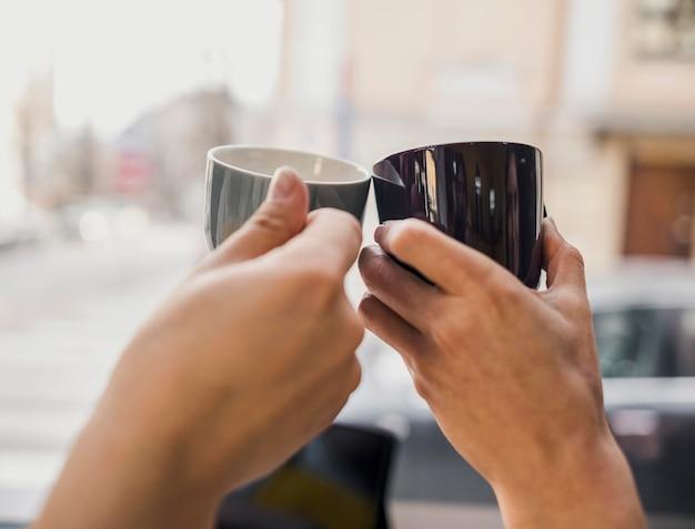 Twee mensen kloppen koffiekopjes samen