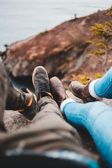 Twee mensen met laarzen die op een klif zitten