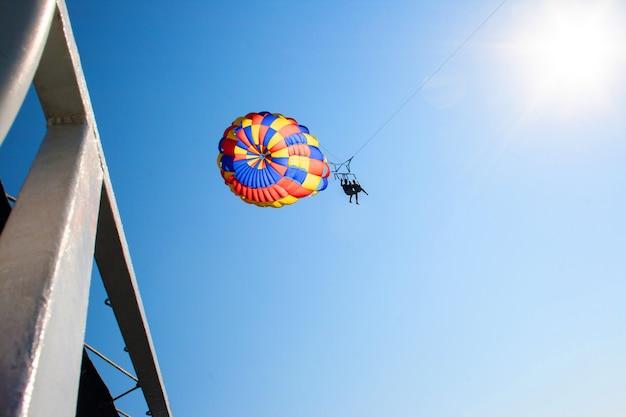 Twee mensen parachutespringen vanaf de betonnen pier boven de zee in de blauwe lucht
