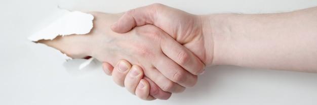 Twee mensen schudden elkaar de hand door een gat in wit papier