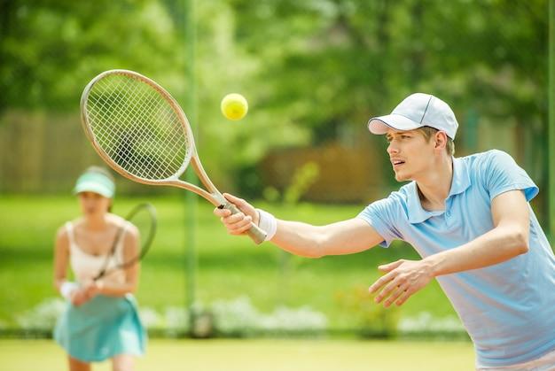 Twee mensen spelen dubbel op de tennisbaan.