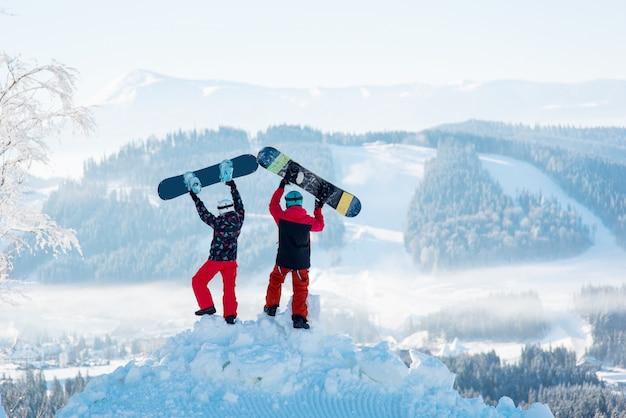 Twee mensen staan met hun rug op een sneeuwbank en heffen hun snowboards op