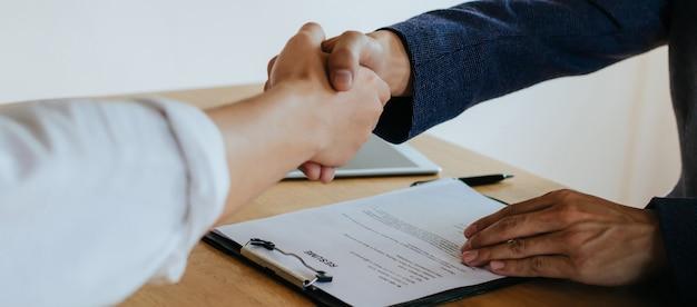 Twee mensen uit het bedrijfsleven de hand schudden na zakelijke sollicitatiegesprek in de vergaderzaal op kantoor