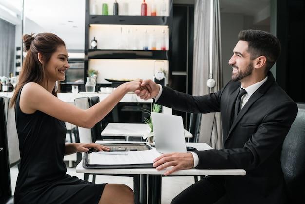 Twee mensen uit het bedrijfsleven hebben vergadering en handen schudden.
