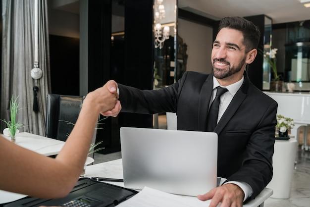 Twee mensen uit het bedrijfsleven hebben vergadering en handen schudden