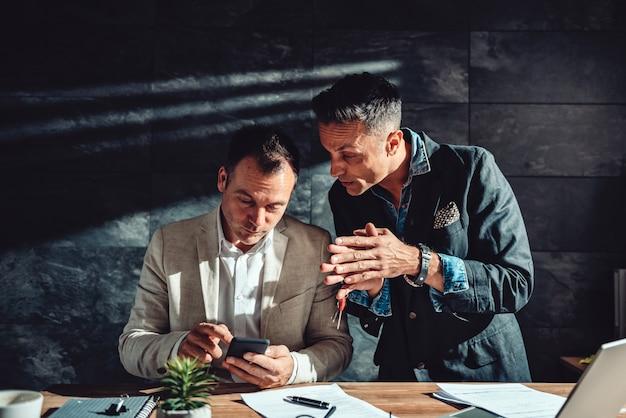 Twee mensen uit het bedrijfsleven met behulp van slimme telefoon
