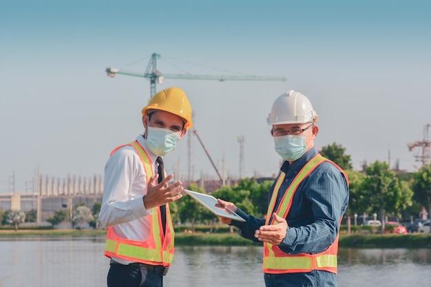 Twee mensen werken aan de bouw van de site en praten dan over een bouwproject