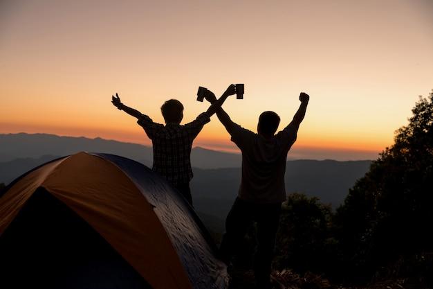 Twee mensentoeristen gelukkig op de bovenkant van de berg bij dichtbijgelegen kampvuur