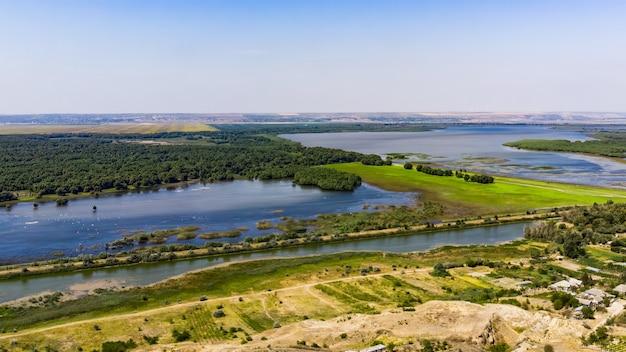 Twee meren met bos en groen veld die ze scheiden, landweg die er vlakbij doorheen loopt