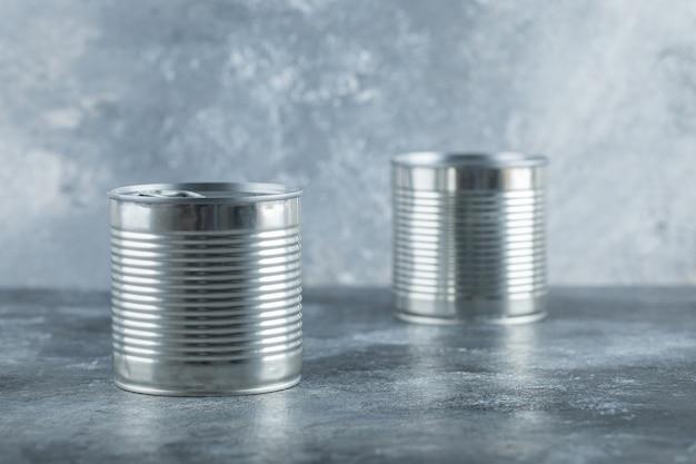 Twee metalen blikken op marmer.