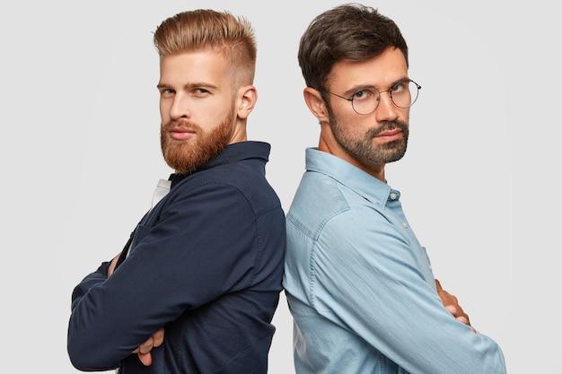 Twee metgezellen staan achter elkaar, kijken serieus naar de camera, houden de armen over elkaar