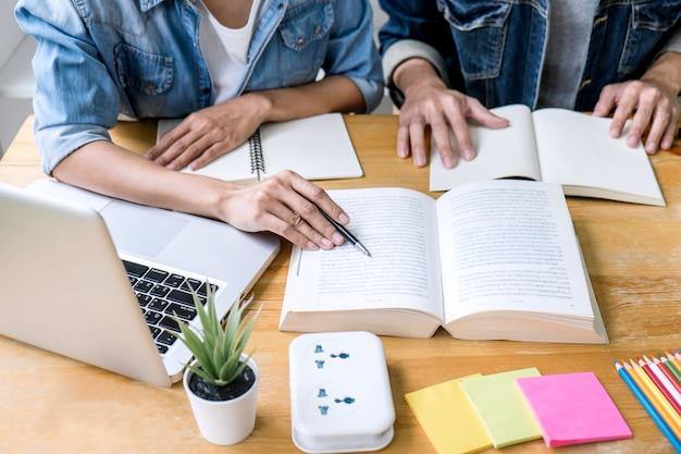 Twee middelbare schoolstudenten met hulpvrienden doen homeworks die in klaslokaal leren