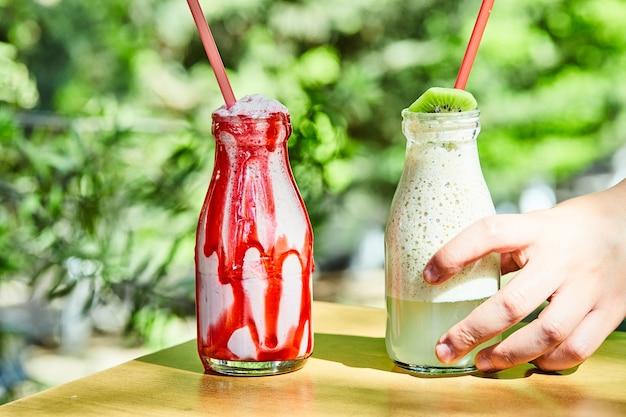 Twee milkshakes die door een hand op houten tafel worden gegrepen
