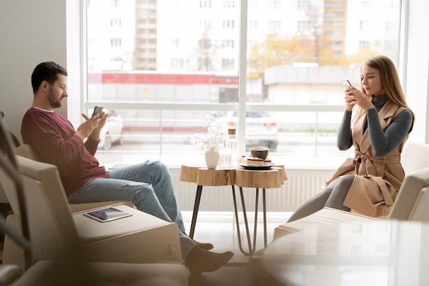 Twee millennials in vrijetijdskleding zitten tegenover elkaar op banken in café tegen raam en scrollen in gadgets