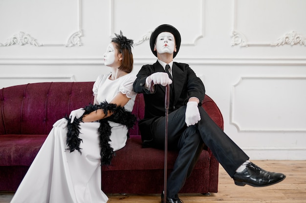 Twee mimespelers, dame en heer zittend op de bank