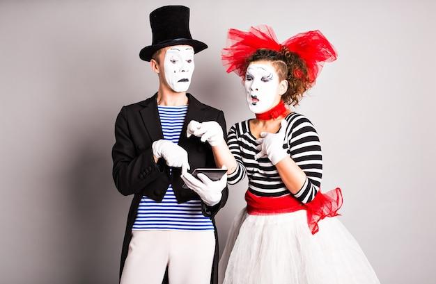 Twee mimespelers gebruik van tablet, april fools day concept.