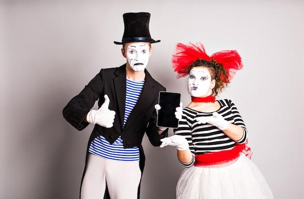Twee mimespelers gebruik van tablet en duim omhoog, april fools day concept.