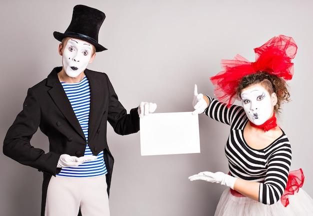 Twee mimespelers met een teken voor reclame, april fools day concept.