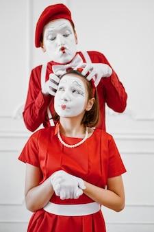 Twee mimespelers met gezicht en handmake-up, rode kostuums