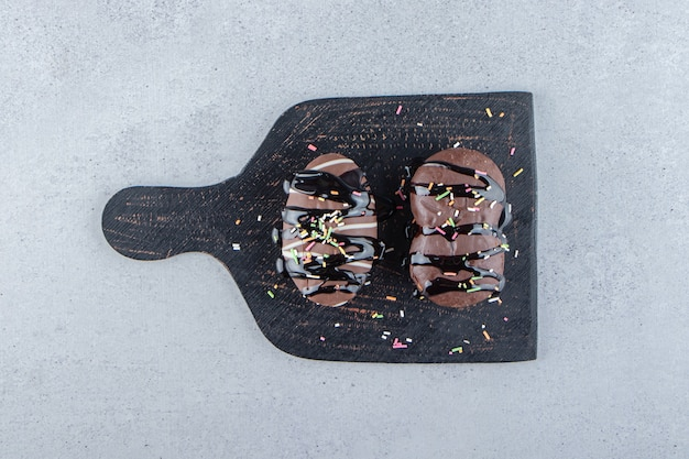 Twee mini-chocoladetaarten met hagelslag op zwarte snijplank. hoge kwaliteit foto