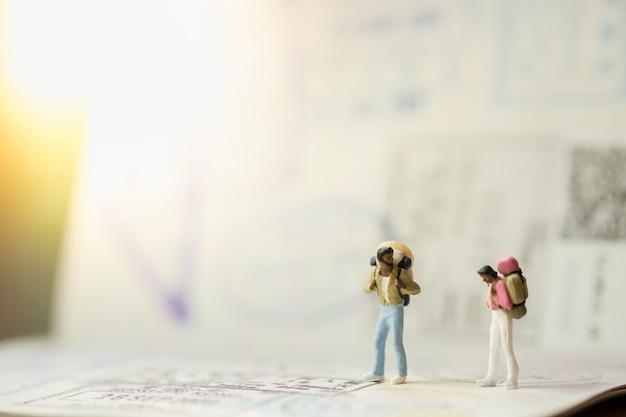 Twee miniatuur mini figuren van reizigers met rugzak staan en praten over paspoort met immigratie stempels